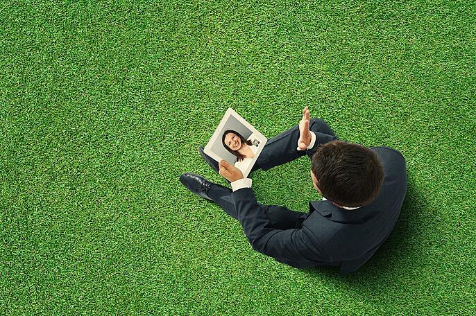 businessman sitting on the green grass, holding tablet pc and waving his hand to young smiley woman
