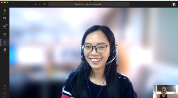Screenshot of a video call with person in headset and blurred background.